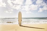 ハワイ ビーチでサーフボードを持つ女性