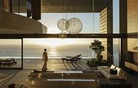 モダンハウスと海を眺める外国人女性