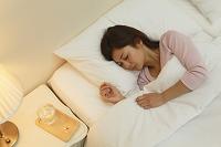 体調不良で寝る日本人女性とテーブルに置かれた薬