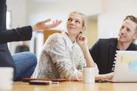 会議室で話を聞く若い女性