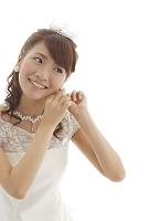 イヤリングをつけるウエディングドレス姿の日本人女性