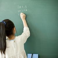 黒板で算数の問題を解く小学生の女の子