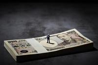 日本円の札束とミニチュア人形