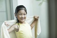 洗濯物のバスタオルを取り入れる日本人の女の子