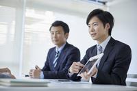タブレットを見せる日本人ビジネスマン