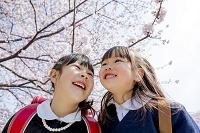 桜の咲く遊歩道で笑う新一年生と新入園児の姉妹