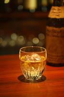 グラスに入ったウイスキーとビン