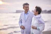 ビーチに佇む日本人シニア夫婦