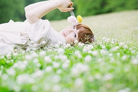 白い花畑に横になる女性
