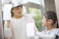 窓拭きをする女の子と母親