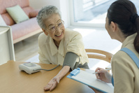 血圧を測るシニアの日本人女性