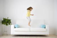 ソファーの上でジャンプする女の子