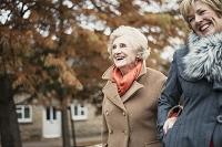 コートを着て外出する笑顔のシニア外国人女性と娘