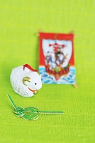 羊の置物と凧と水引細工と緑の背景