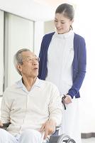 車椅子のシニア患者と看護師