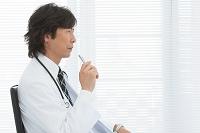 ペンを持って座っている医師