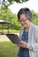 公園でタブレットを見るシニア日本人女性