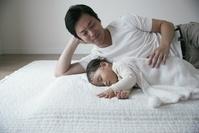 赤ちゃんと添い寝をする父親