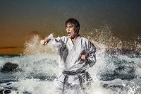 荒波で空手の突きをする日本人男性