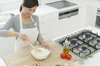 明るいキッチンで料理する日本人女性