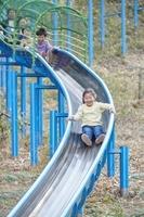 滑り台で遊ぶ日本人家族