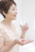 手の平に薬をのせた中高年日本人女性