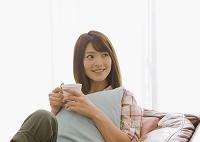 ソファに座ってくつろぐ日本人女性