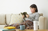 マスクをつけて本を読む日本人女性