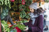 クリスマスマーケットで買い物する女性