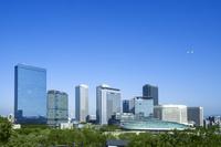 大阪ビジネスパークのビル群と大阪城ホール上空の飛行機