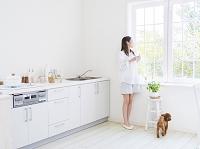 キッチンに立つ日本人女性とトイプードル 犬