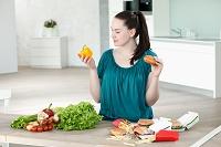 野菜とファーストフードを選ぶ女性