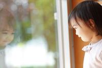 窓辺から遠くを見る日本人の女の子