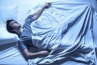ベッドで眠る外国人男性