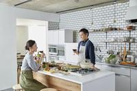 ワインを飲みながら料理をする日本人夫婦
