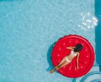 プールに浮かぶ水着の女性
