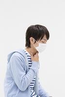 マスクをして喉に手をあてる若者日本人男性