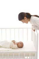 ベビーベッドの赤ちゃんを見守るお母さん