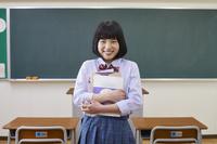 教科書を持つ笑顔の女子高生