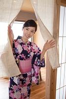 浴衣で暖簾をくぐる若い女性