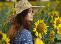 夏のひまわり畑に立つ女性