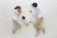 ブランケットに寝そべる赤ちゃんと両親