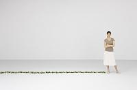 植物の横に立つ女性