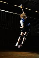 ネット際でジャンプするバレーボール選手