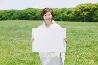新緑とホワイトボードを持つシニア日本人女性