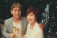 シャンパンで乾杯する日本人のシニア夫婦