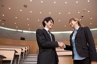 握手をするスーツの日本人男性と外国人女性