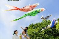 公園で息子を肩車して鯉のぼりを見上げる日本人家族