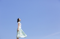 青空の下に立つ日本人女性