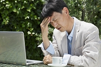 頭痛で頭を押さえる中年日本人男性